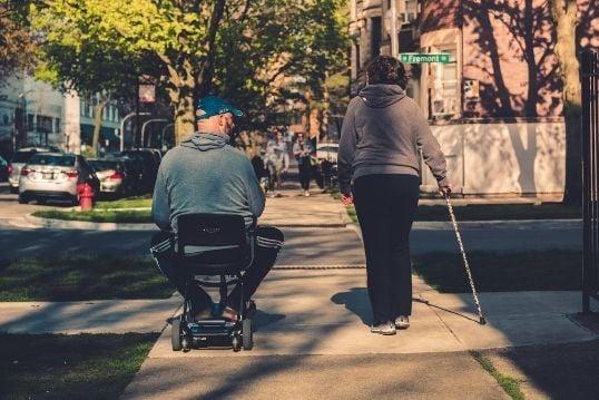 Man en vrouw lopen over straat met een rolstoel en wandelstok
