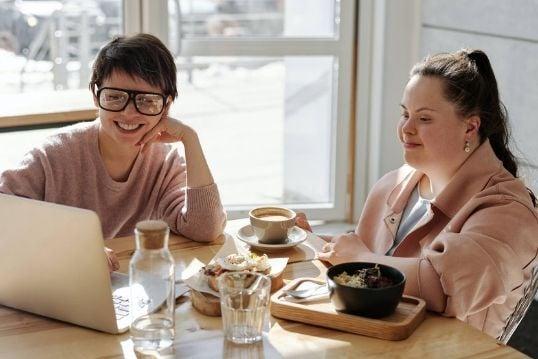 Twee meisjes aan tafel met koffie en een laptop