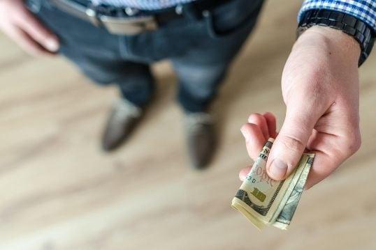man heeft een paar briefjes geld in zijn handen opgevouwen