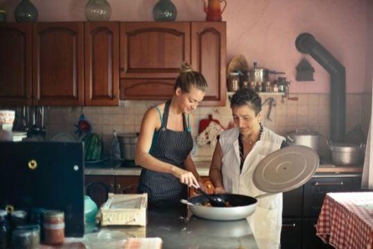 Twee vrouwen met een schort aan zijn samen aan het koken.