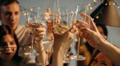 des gens trinquent avec un verre de vin blanc a une fête