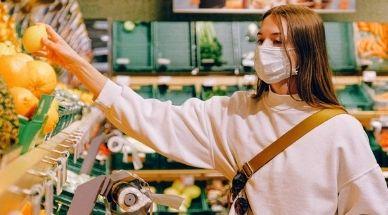 Une fille fait les courses et tient une orange en main. Elle porte un masque.