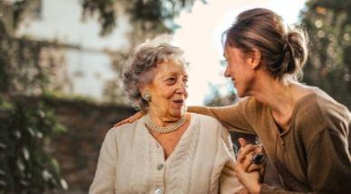 Une personne âgée et une jeune femme s'embrassent dans un parc avec un sourire au visage