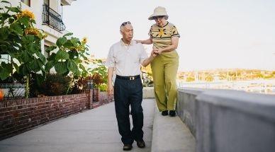 Man ondersteunt vrouw terwijl ze op een verhoging loopt.