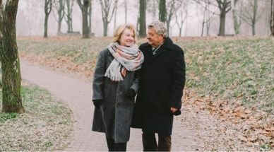 un couple marche bras dessus bras dessous dans une forêt en l'hiver