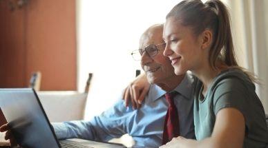 Opa en kleindochter zitten samen achter de laptop aan een tafel